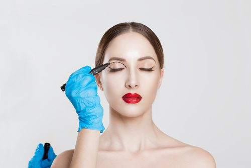 eyelid reduction double eye lid removal plastic surgery cosmetic operation concept woman eyes closed doctor surgeon hand in gloves -img-blog