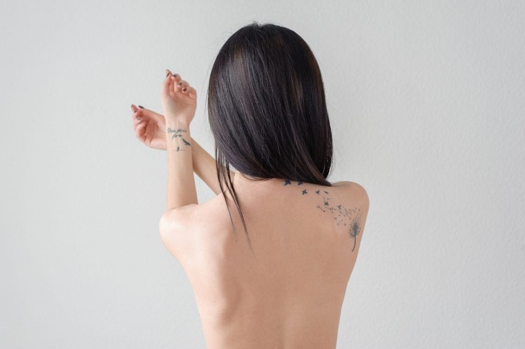 the back of a girl with a tattoo