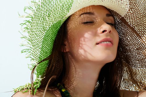 close-up of a girls face in straw hat enjoying the sun-img-blog