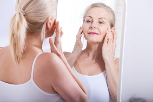 middle aged woman looking at wrinkles in mirror-img-blog