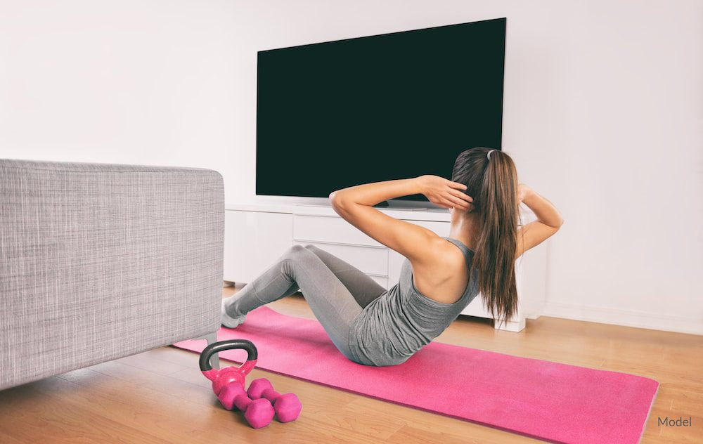 Woman exercising at home, potentially after plastic surgery.