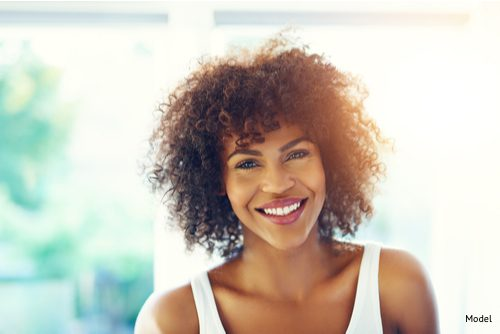 woman smiling after choosing the right facial rejuvenation technique for her.
