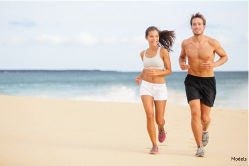 Young couple running on beach. Man enjoying run with no shirt on after male breast reduction-img-blog