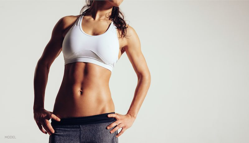 Close up of fit woman's torso with her hands on hips