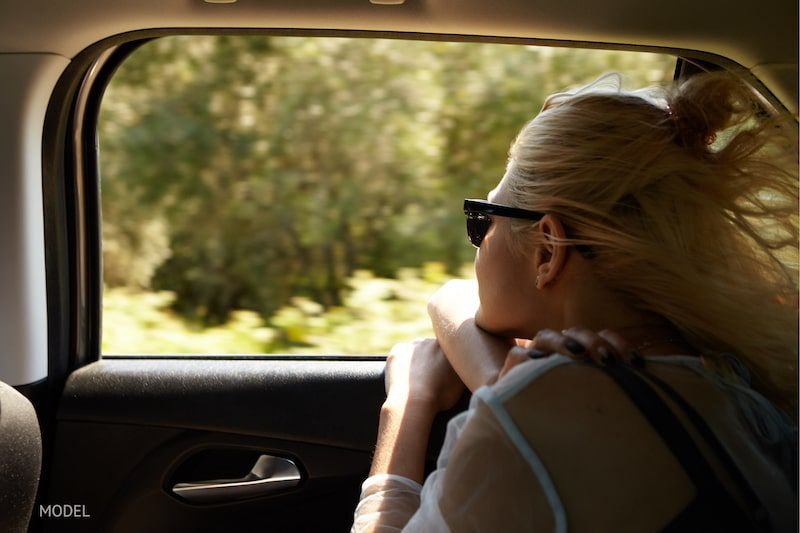 Woman looking out of a car window while on a road trip.