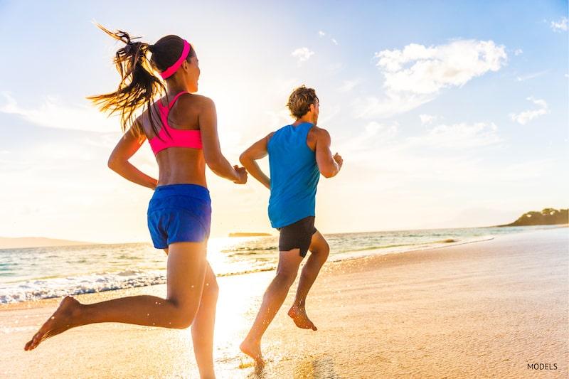Couple running on a sunny beach.