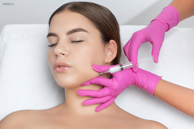 Young woman getting an injectable placed in her jaw by a female practitioner, wearing bright pink gloves.