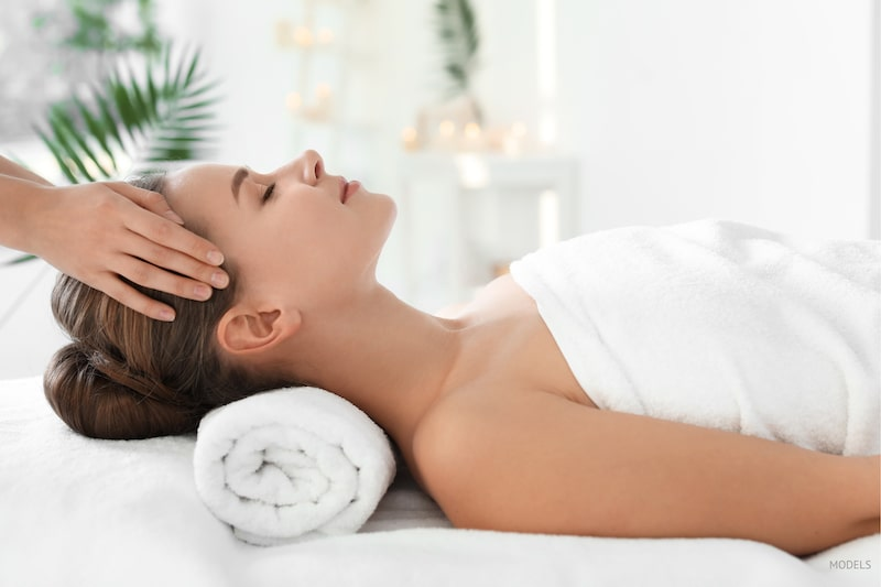 Woman getting her face and temples massaged.
