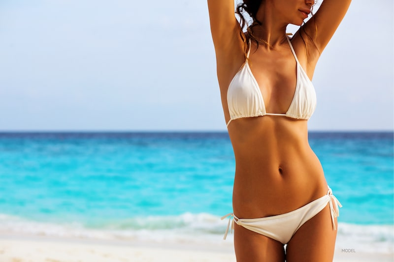 Fit woman in white bathing suit standing on the beach with her arms above her head.